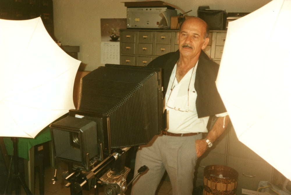 """Israeli photographer, David Harris, in his 'studio' in the basement of the Palacio de Liria, Madrid. He stands behind a large-format Sinar monorail camera and umbrella flash heads. <small>Image © Copyright 2021 Facsimile Editions Ltd.  For use visit: <a href=""""https://www.facsimile-editions.com/copyright/"""">Copyright T&C Facsimile Editions Ltd</a></small>"""