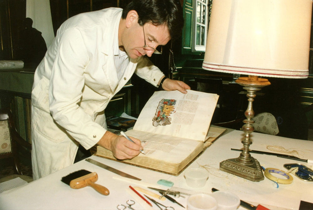 """James Brockman, renowned bookbinder, prepares the manuscript prior to disbinding for photography. <small>Image © Copyright 2021 Facsimile Editions Ltd.  For use visit: <a href=""""https://www.facsimile-editions.com/copyright/"""">Copyright T&C Facsimile Editions Ltd</a></small>"""