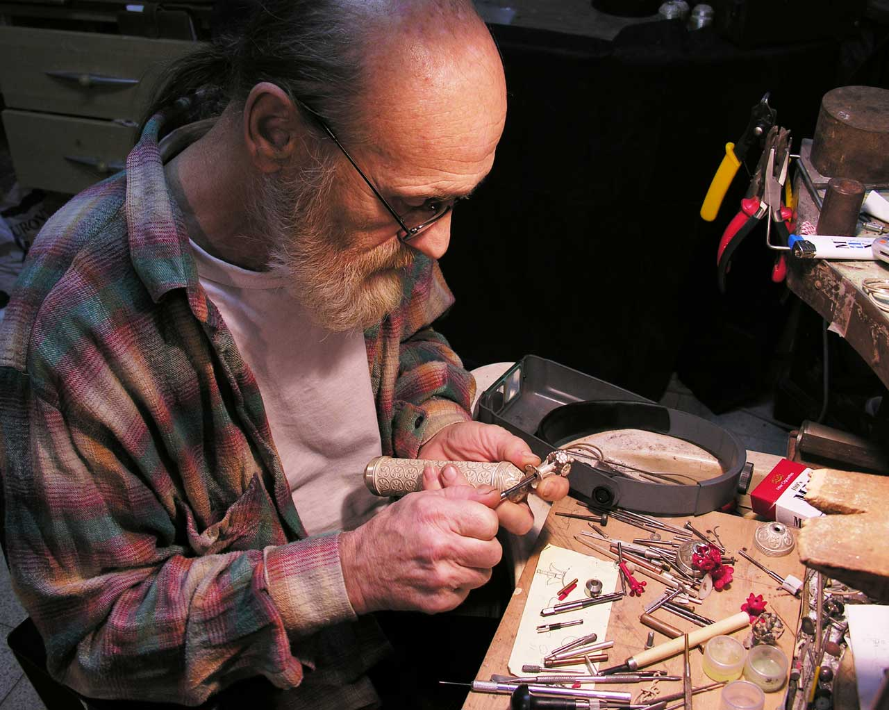 """The silversmith at work <small><a href=""""https://www.facsimile-editions.com/copyright/"""">© Copyright 2021 Facsimile Editions Ltd</a></small>"""